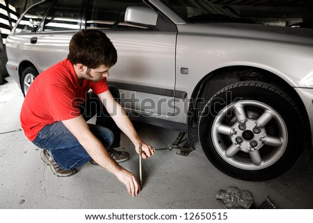 A male jacks up a car in a garage - fixing the wheel