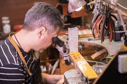 A male jeweler looks through a microscope and fixes a gem on a pendant