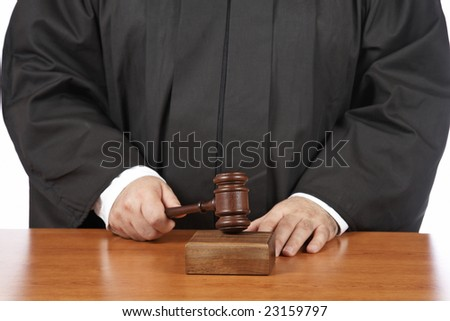 A male judge in a courtroom striking the gavel. Shallow depth of field