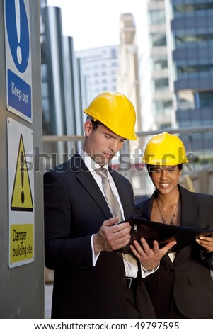 A male manager on a construction site wearing a hard hat and talking with his Asian female colleague