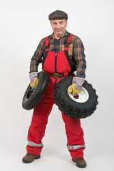 A male mechanic dressed in a red bib overall is standing on a white background with two wheels from the tractor and does not know which one to choose.