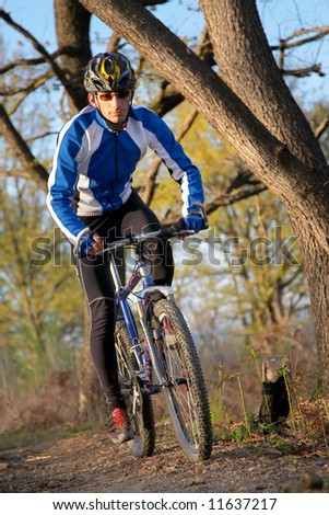 A male mountain biker on a single track trail in the woods.