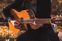 A male musician plays an acoustic guitar at a wedding for live music
