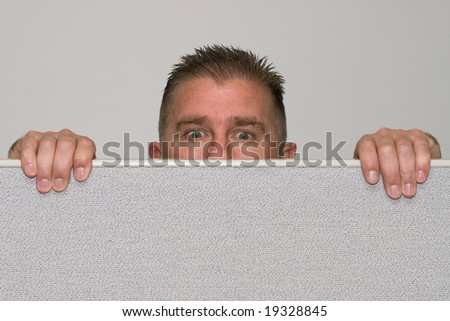 A male office worker peers over a cubicle because he is nosy. - stock photo