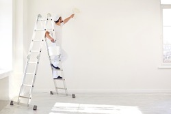A male painter in a white uniform with a roller works in his hand in a white room