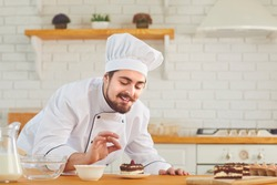 A male pastry chef works decorating a cake on a kitchen bakery