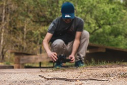 A male photographer takes a photo of a copperhead snake with a DSLR camera. The snake is one of the most venomous species in the United States.