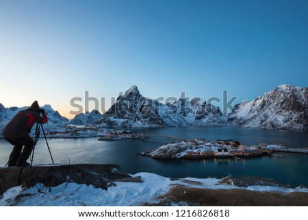 A male photographer uses camera and tripod to capture a beautiful landscape picture at twilight in Lofoten. Winter  scenery with snow-covered mountains, fjord and the fisherman's cabins at Sakrisøy