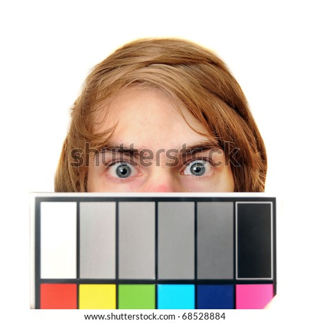 A male production assistant holds up a white balance card with test colors on it to calibrate the colors for photography and videography.