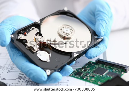 A male repairman wearing blue gloves is holding a hard drive from computer or laptop in hands. Performs fault diagnostics and performs urgent repairs recovery of lost data during deletion HDD closeup