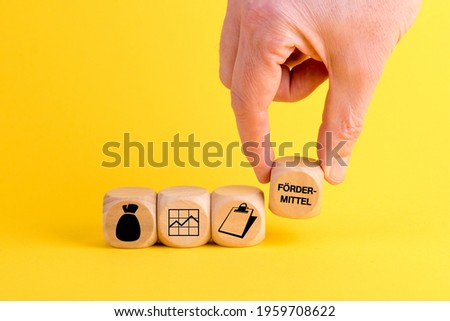 A male's hand arranging wooden blocks with money, line graph, clipboard, and funding icons-concept for business growth process Photo stock ©