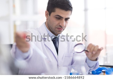 A male scientist holding a magnifying glass in a research laboratory