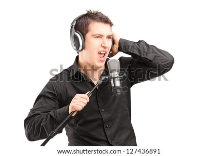 A male singer with headphones performing a song isolated on white background