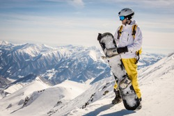 a male snowboarder in bright clothes stands against the background of the mountains. good weather. the sun is shining