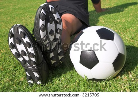A male soccer (football) player, referee or coach sitting next to a soccer ball. The image is of feet and legs, with soccer togs, and a black and white ball. Focus on soccer ball and heels