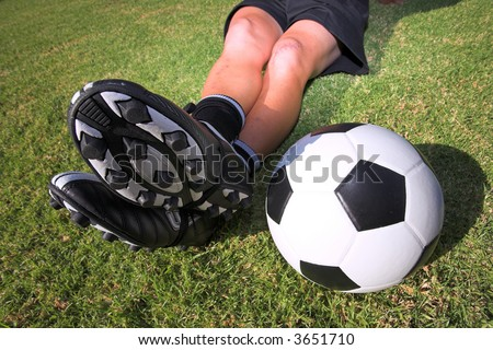 A male soccer (football) player, referee or coach sitting with crossed legs. Focus on ball and togs