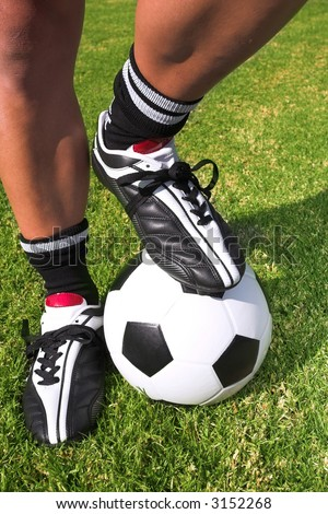 A male soccer (football) player, referee or coach standing with one foot on a soccer ball. The image is of feet and legs, with soccer togs, and a black and white ball