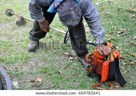 A male start the machine with pulling the wire #604782641