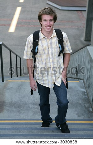 A male student climbing the stairs to go to school to get an education - stock photo