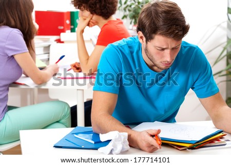 A male student reading his notes while studying at university