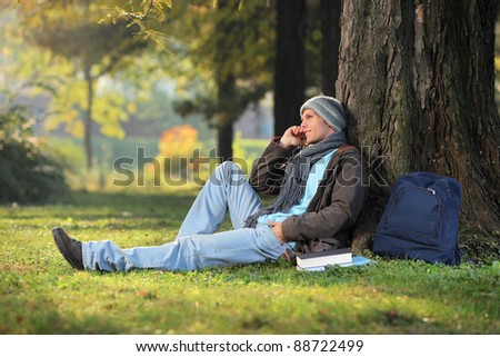 A male student talking on a phone seated on a grass in the city park