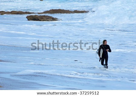 A male surfer after a surf walking through the waves up to the beach