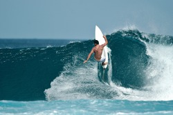 A male surfer executes a radical move on a beautiful ocean wave.