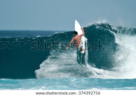 A male surfer executes a radical move on a beautiful ocean wave. #374392756