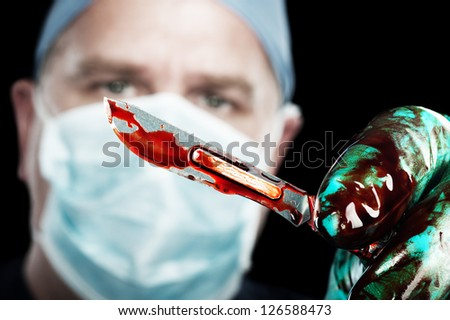 A male surgeon holds up a sharp, bloody scalpel during surgery