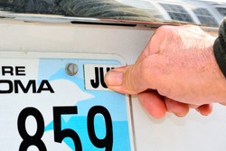 A male thumb pressing the required month tag for an annual license registration on rear license plate.