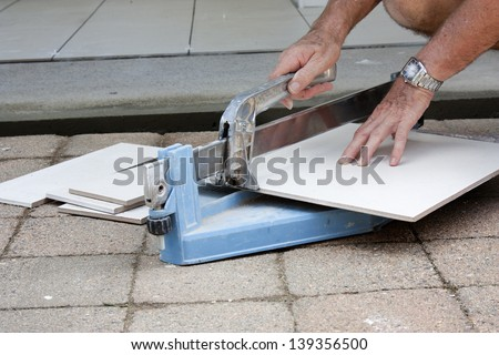 a male tiler cutting ceramic tiles with a tile cutter