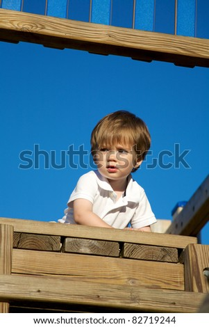 A male toddler playing on an outdoor playground