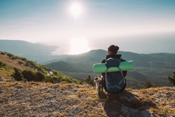 A male tourist meets a dawn in the mountains. Hiking. A young handsome guy climbed to the top of the mountain in the morning and sits on the edge of a cliff with his friend cat.