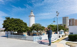 A male tourist photographs the white lighthouse at the port of Malaga in Andalusia. It's a summer day with blue skies. There are some blue benches.