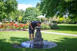 A male tourist stops in a city park to have a drink of cold water at a drinking fountain