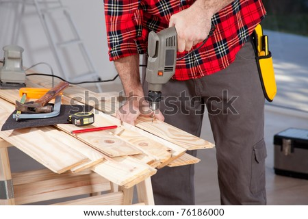 A male using an electric hand drill on a plank