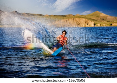 A male waterskiing on a beautiful lake