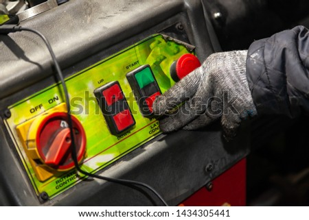 A male worker in working gloves presses the red button on the machine control panel in a workshop or factory. Industry and production in engineering. #1434305441