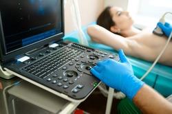 A mammologist makes breast ultrasound scanning