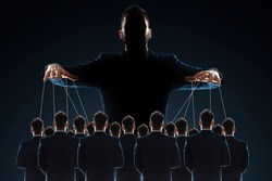 A man, a puppeteer, controls the crowd with threads. The concept of world conspiracy, world government, manipulation, world control