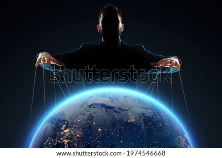 A man, a puppeteer, manipulates the planet. The concept of world conspiracy, world government, manipulation, world control Stockfoto ©