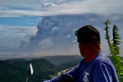 A man aboard a motorcycle pauses to watch Taal Volcano as it spews ash after becoming active on January 11.