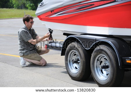 A Man Adjusting Tie Down Straps On Boat Trailer