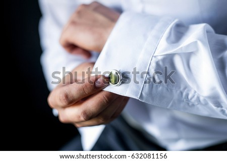A man adjusts his cuff on a white shirt. The guy straightens the sleeve. Close-up of sleeves.