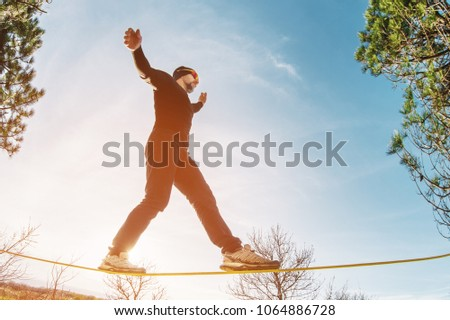 A man, aged with a beard and wearing sunglasses, balances on a slackline in the open air between two trees at sunset #1064886728