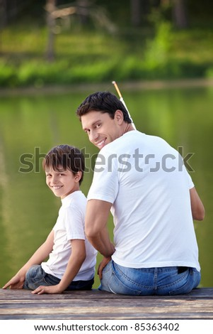 A man and a boy with a fishing rod on the lake