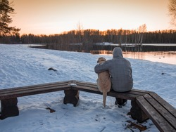 A man and a dog are sitting on a bench hugging and contemplating the sunset