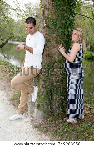 a man and a pregnant woman play in the park  #749983558