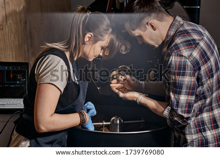 A man and a woman are busy roasting coffee on the background of a roasting machine. The roasting master shows the student roasted coffee beans. Coffee manufactory. coffee bean roasting workshop