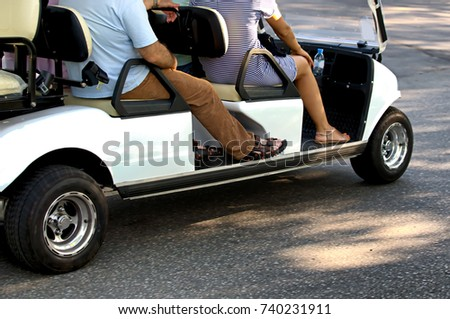 A man and a woman are driving along a road in a park in an electric golf cart. The concept of urban style, ecology, comfort. #740231911